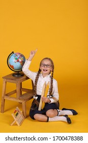 Caucasian first grader with long braids on a yellow background with a globe with the image of Africa, Europe, America