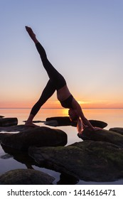 caucasian fitness woman practicing yoga on the beach at sunset