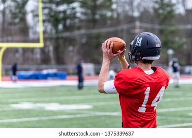 A caucasian football player is catching a ball