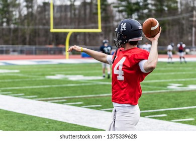 A caucasian football player is thrawing a ball