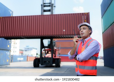 Caucasian foreman man is using walkie talkie to command his workers with crane lifting container in background in container depot terminal.