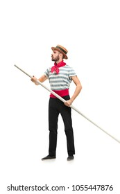 Caucasian funny bearded man in traditional gondolier costume and hat with paddle standing and posing at studio isolated on white background. Serious young man looking away. Profile. Human emotions