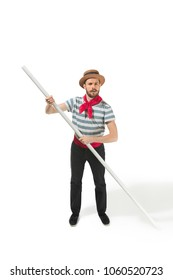 Caucasian funny bearded man in traditional gondolier costume and hat with paddle standing and posing at studio isolated on white background. Side view of young man. Human emotions, facial expression