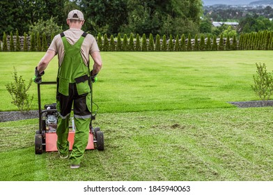 Caucasian Gardener in His 40s and His Powerful Gasoline Lawn Aerator Job For Controlling Lawn Thatch, And Reducing Soil Compaction. Garden Technologies.