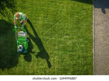 Caucasian Gardener Moving Lawn Aerial Photo.  Landscaping Business. Industrial Theme.