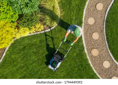 Caucasian Gardener Mowing Backyard Garden Grass Using Cordless Electric Grass Mower. Aerial View. Gardening and Landscaping Industry.