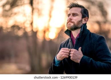 Caucasian gentleman adjusting his pea coat and maroon scarf staring off to his right with the sun setting behind him during golden hour outdoors.