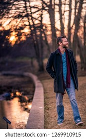A caucasian gentleman wearing a blue shirt, maroon scarf, and dark peacoat taking a stroll along the pond, staring to his left with the sun setting in the background during golden hour.