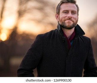 Caucasian gentleman wearing a pea coat and maroon scarf positioned to his left while smiling lips closed with the sun setting behind him during golden hour outdoors.