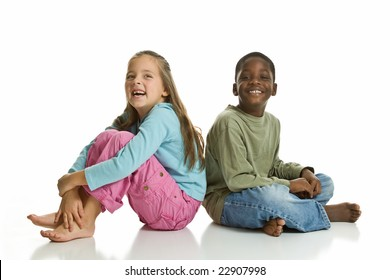 A Caucasian girl and an African American boy smiling for the camera. Isolated on a white background.