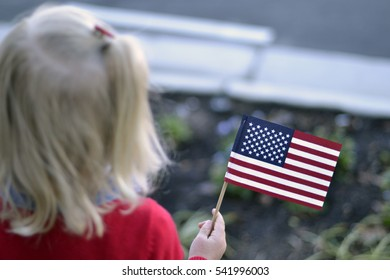 Caucasian Girl with Blonde Hair Holding a Tiny American Flag while Watching a Parade