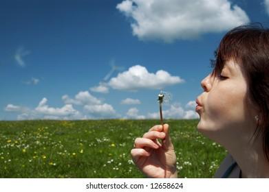 caucasian girl blowing to dandelion