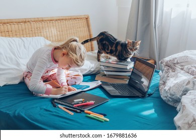 Caucasian girl child sitting in bed and learning online on laptop Internet. Virtual class lesson on video during self isolation at home. Distant remote video education. Modern school study for kids.