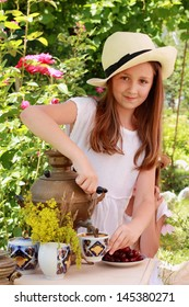 Caucasian girl drink tea from an old Russian samovar in the garden in the street/Russian national traditions