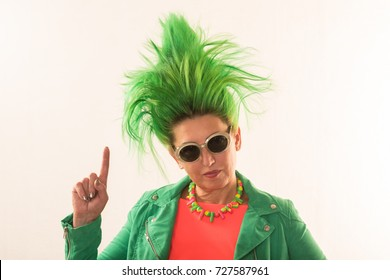 A caucasian girl in a green dress and with green hair is preparing for the holidays. Suit of the teacher of primary classes. The concept of happy holidays and good mood.