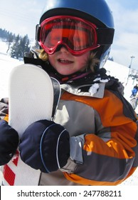caucasian girl in helmet holding skis in the winter mountain