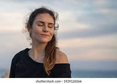 Caucasian girl with her eyes closed enjoying the sun and the sunset on the promenade in Palma de Mallorca, Spain (Perfect for copyspace)