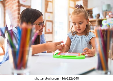 Caucasian girl kid playing and learning at playschool with female teacher. Mother and daughter at playroom around toys drawing on magnetic blackboard