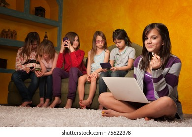 Caucasian girl with laptop while friends are busy with handheld devices