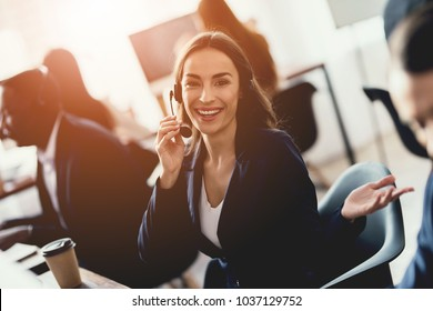 Caucasian girl looks at work in the call center. She answers customer calls. She's in a good mood. Call center concept.