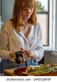 Caucasian girl in a modern kitchen, prepares some vegetables
