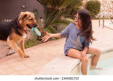 Caucasian girl playing with her dog on the pool side.