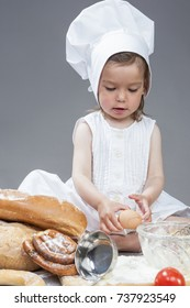 Caucasian Girl In Specific Cook Uniform Breaking Down Fresh Egg and Making Food in Kitchen Glassware with Whisk In Studio Environment. Against Gray Background. Vertical Shot