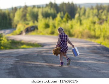 Caucasian girl walking away alone on an empty highway with bear and suitcase. Concept image of a runaway child with loneliness and sad feelings.