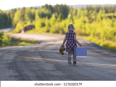 Caucasian girl walking away alone on an empty highway with bear and suitcase. Concept image of a runaway child with loneliness and sad feelings. Image has a vintage effect.
