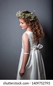 Caucasian girl wearing first holy communion dress. Girl preparing to take first communion. First Communion Day. Studio photo.