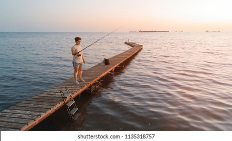 Caucasian girl woman sitting on a wooden pier with a fishing rod. He stands knee-deep in the water and catches fish. a saturated Sea Sunset