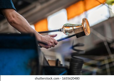 Caucasian glassblower artist is shaping the molten glass extracted from the furnace located in a glass factory in Romania where each piece is manually made by the artisans hands. Labour day.