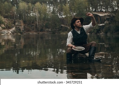 caucasian gold digger in retro clothes washes gold in metal bowl in lake with rocky bank. He wears hat, shirt, leather pants, vest, boots. He sits on the rock in the water. Sky is cloudy and grey.