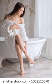 Caucasian gorgeous woman with long legs with smooth soft skin without hair, using body lotion after epilation procedure in beauty spa