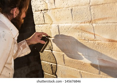 Caucasian graffit artist working on mural with spray paint