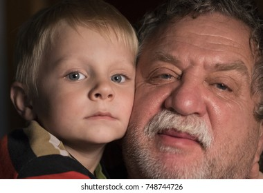 Caucasian grandfather with grandson looking at camera