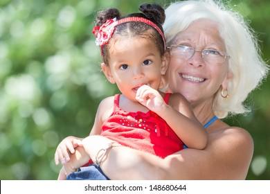 Caucasian grandmother carrying her small latin granddaughter