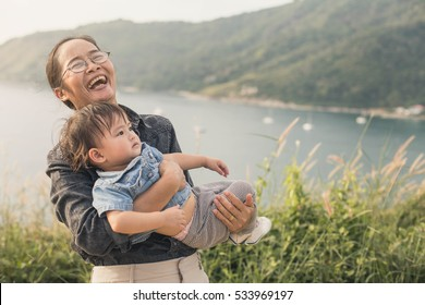 Caucasian grandmother carrying her small granddaughter on top of the hill.