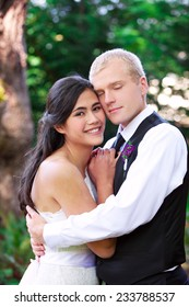Caucasian groom holding his biracial bride, smiling. Diverse couple.