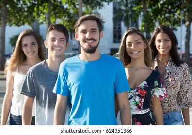 Caucasian guy with beard with hispanic and latin men and woman