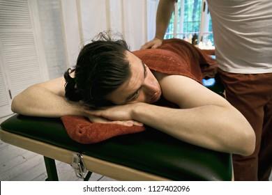 Caucasian guy laying down on massage couch. Closeup horizontal shot