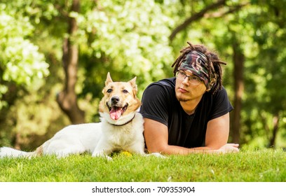 caucasian guy is laying on the grass with his dog