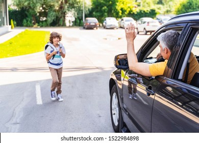 Caucasian guy waving with hand to little son near car. Family relationship concept