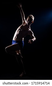 Caucasian half naked male dancer exercising a contemporary dancing isolated on black wall