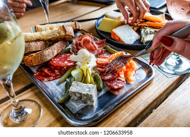 Caucasian hand holding a fork next to a platter of deli meat, bread and pickled vegetables on a silver platter on a wooden table.