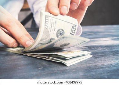 Caucasian hands counting dollar bills on darw wooden table