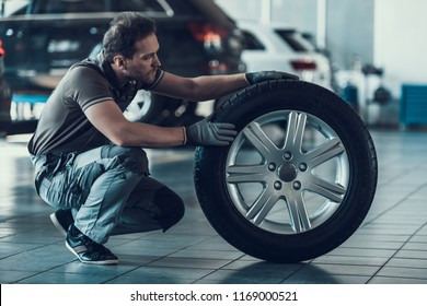 Caucasian Handsome Auto Mechanic Cheking Car Wheel. Portrait of Adult Machinist Doing Wearing Uniform Work in Garage. Technic occupation. Automobile Repair Service Concept.