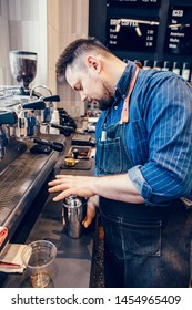 Caucasian handsome bearded man barista making iced coffee cappuccino latte. Waiter server shaking metal silver jar cup to make cold drink. Small business and person at work concept.