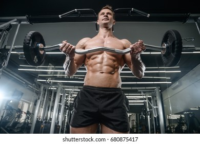 Caucasian handsome fitness model training in the gym. Man on diet flexing muscles and six pack abs