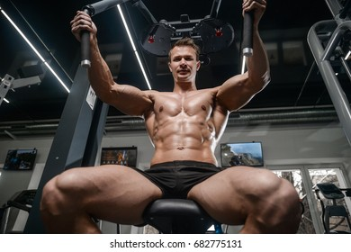 Caucasian handsome fitness model training in the gym.Man on diet flexing muscles and six pack abs